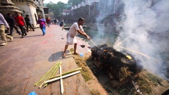 Cremation fire with smoke on Bagmati river bank. Pashupatinath Temple, Kathmandu Stock Footage