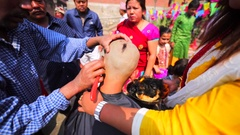 Shaving teenager's head at Upanayana ceremony. Pashupatinath Temple. Kathmandu Stock Footage