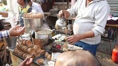 Man preparing Indian Masala tea chai latte in Varanasi Stock Footage