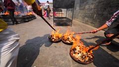 Men poke the sacral fire at Upanayana ceremony. Pashupatinath Temple. Kathmandu Stock Footage