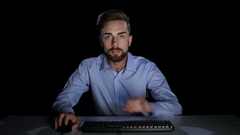Man excitedly looking at a computer monitor. Dark studio Stock Footage