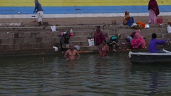 People at holy ghats among ancient hindu temples in the morning in Varanasi Stock Footage