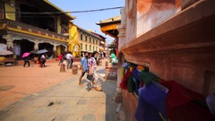 Entrance of the Boudhanath stupa, lion statue, prayer wheel, tourists. Kathmandu Stock Footage