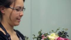Brunette florist makes bouquet flower composition inside Stock Footage