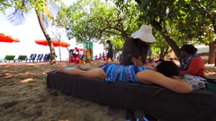 Tourists relaxing on a beach. Beach sellers offering massage. Kuta Stock Footage