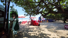 Tourists relaxing on a beach. Kuta Beach famous resort in Bali. Stock Footage