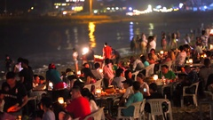 Tourists relaxing in the restaurant and at a beach. Jimbaran beach restaurant. Stock Footage
