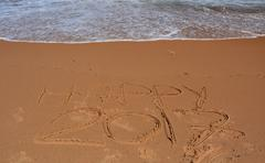 """Happy 2017 lettering on the beach. """"Happy 2017"""" drawn on sand on a beach. Stock Photos"""