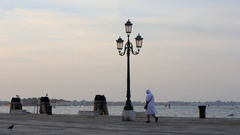A nun walks along the Riva degli Schiavoni in slow motion, Venice, Italy. Stock Footage