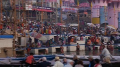 Boats at river Ganga and people at holy ghats among ancient hindu temples Stock Footage