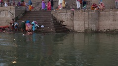 People at holy ghats among ancient hindu temples Stock Footage