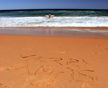 """Merry Christmas lettering on the beach. """"Merry Xmas"""" drawn on sand on a beach Stock Photos"""
