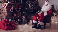 Santa Claus sitting in front of a fireplace near a Christmas tree with sack full Stock Footage