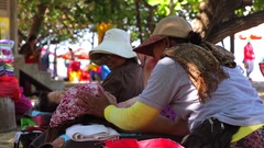 Tourists relaxing on a beach. Beach sellers. Kuta Beach famous resort in Bali. Stock Footage