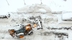 Backhoe loader shovel snow on road, turn and dump off to snowbank at roadside Stock Footage