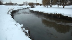 Shallow dirty channel run between snowy banks, vapour rise from gurgling water Stock Footage
