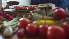 Woman adding basil leaves and olive oil on sliced tomatoes Stock Footage