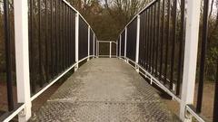 Walking along a black and white bridge. Stock Footage