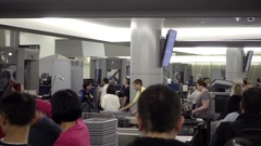 Passengers putting personal items on trays in security check at San Francisco Stock Footage