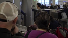 Panning people as they wait on crowded long line for security check in airport Stock Footage