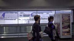 Man and woman texting on smartphone walking past interior window SFO airport Stock Footage