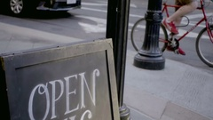 Open mic sign on chalkboard in street outside bar with guys on bicycle Stock Footage