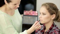 Makeup artist applies makeup brush Stock Footage