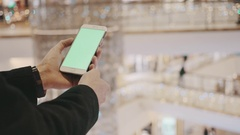 Male hands using smartphone with green screen in shopping mall. Holiday Stock Footage
