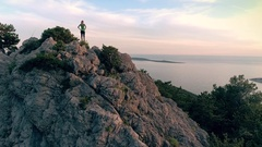 Aerial - Moving above young adult woman reaching the top of the seaside mountain Stock Footage