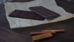 Sweet chocolate with cacao powder on wooden background. Dark chocolate bar Stock Footage