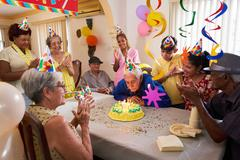 Family Reunion For Birthday Party Celebration In Retirement Home Stock Photos