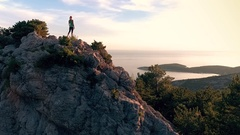 Aerial - Moving above woman standing on rock mountain at seaside Stock Footage
