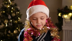 4k, funny boy in red het  stands near the Christmas tree 1 Stock Footage