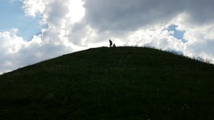 A couple on top of a grass hill - woman taking hand of the man to help him stand Stock Footage