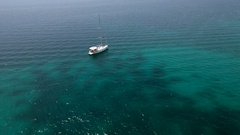 Aerial - Flyover sail boat anchored in transparent blue water Stock Footage