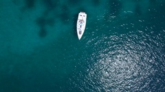 Aerial - Top down view of a sail boat anchored in transparent blue water Stock Footage