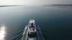 Aerial - Flying behind the luxury yacht with a helicopter in late afternoon Stock Footage