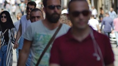 Men in dark glasses, walking up one by one on busiest streets of the city Stock Footage