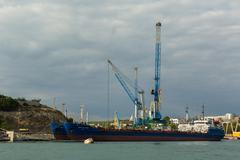 Tanker for the transport of oil and minerals near lifting cargo cranes Stock Photos