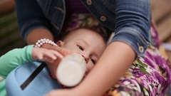 Mother feeds baby from a bottle in his lap. Close-up Stock Footage