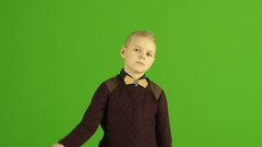 The cute boy thumb down on the green background Stock Footage