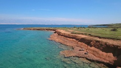 Aerial - Flying low above the coast of red  soil with turquoise color water Stock Footage