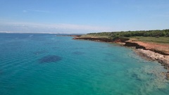 Aerial - Flying low above turquoise sea water near the coast of red earth Stock Footage