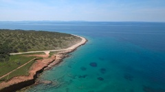 Aerial - Flying high above the coast with a road along the sea on sunny day Stock Footage