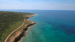 Aerial - Flying high above turquoise sea water near the coast of red earth Stock Footage
