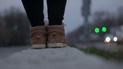Female feet in black shoes walk on the asphalt blurred lights Stock Footage