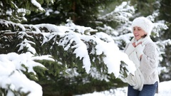 Attractive female beats the fir-tree's branch and shakes off a snow Stock Footage