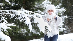 Knitted sweater and fur hat dressed attractive female throwing snowballs Stock Footage