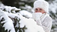 Knitted sweater and fur hat dressed attractive female warm up her frozen fingers Stock Footage