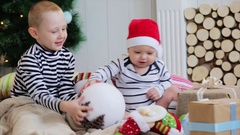 Good New Year spirit. happy children sitting in a festive Christmas tree. Stock Footage
